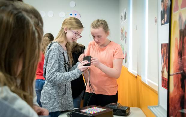 Friends Brooke Allen and Ellee Hinckley, both sixth-graders, work together to try to figure out the clues and puzzles in the 1980s themed escape room at the Rifle Library. The exercise encourages students to