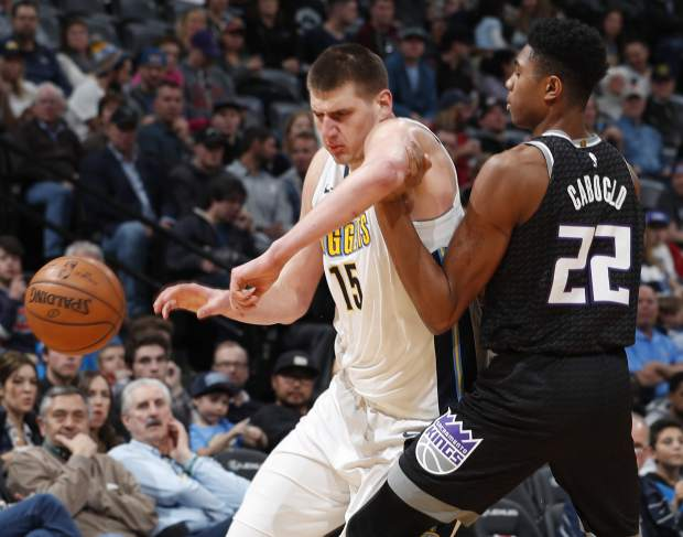 Denver Nuggets center Nikola Jokic, left, loses control of the ball as he is fouled by Sacramento Kings forward Bruno Caboclo in the second half of an NBA basketball game Sunday, March 11, 2018, in Denver. (AP Photo/David Zalubowski)