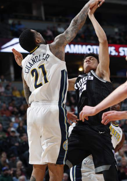 Denver Nuggets forward Wilson Chandler, left, fouls Sacramento Kings forward Justin Jackson as he drives the lane to the basket in the first half of an NBA basketball game Sunday, March 11, 2018, in Denver. (AP Photo/David Zalubowski)