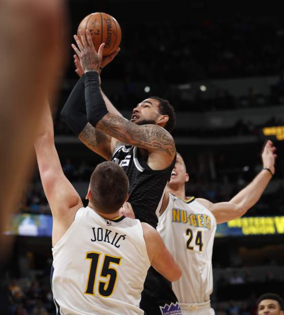 Sacramento Kings center Willie Cauley-Stein, center, center, is fouled as he goes up for a basket by Denver Nuggets center Mason Plumlee, right, as forward Nikola Jokic, left, defends in the first half of an NBA basketball game Sunday, March 11, 2018, in Denver. (AP Photo/David Zalubowski)