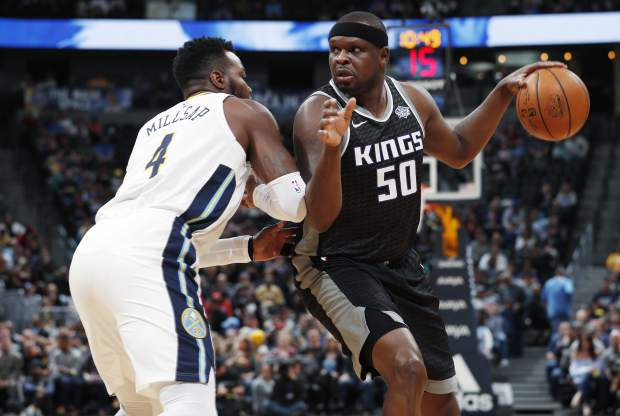 Sacramento Kings forward Zach Randolph, right, works the ball past Denver Nuggets forward Paul Millsap for a shot in the first half of an NBA basketball game Sunday, March 11, 2018, in Denver. (AP Photo/David Zalubowski)