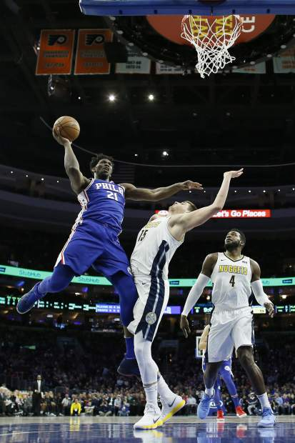 Philadelphia 76ers' Joel Embiid (21) goes up for a shot against Denver Nuggets' Nikola Jokic (15) during the first half of an NBA basketball game, Monday, March 26, 2018, in Philadelphia. (AP Photo/Matt Slocum)