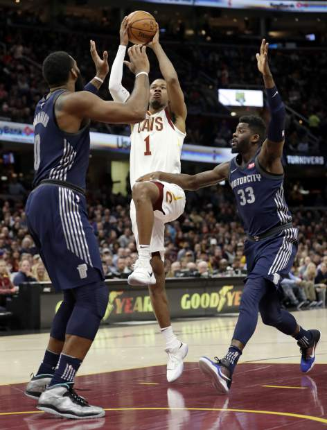 Cleveland Cavaliers' Rodney Hood (1) drives between Detroit Pistons' Andre Drummond (0) and James Ennis (33) in the first half of an NBA basketball game, Monday, March 5, 2018, in Cleveland. (AP Photo/Tony Dejak)