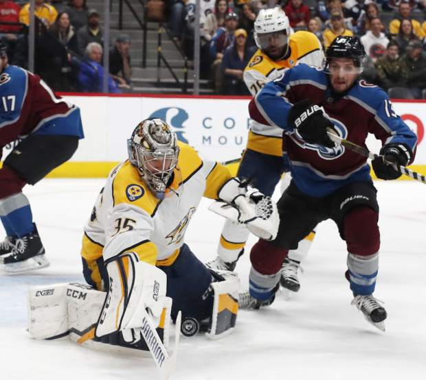 Nashville Predators goaltender Pekka Rinne, left, makes a stick-save of a shot by Colorado Avalanche center Alexander Kerfoot, right, as Predators defenseman P.K. Subban, back, covers in the first period of an NHL hockey game Sunday, March 4, 2018, in Denver. (AP Photo/David Zalubowski)