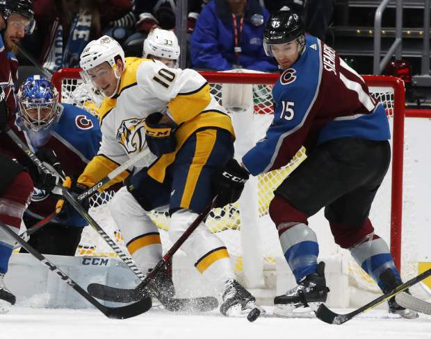 Nashville Predators center Colton Sissons, center, has his shot blocked by Colorado Avalanche goaltender Semyon Varlamov, left, as defenseman Duncan Siemens covers in the first period of an NHL hockey game Sunday, March 4, 2018, in Denver. (AP Photo/David Zalubowski)