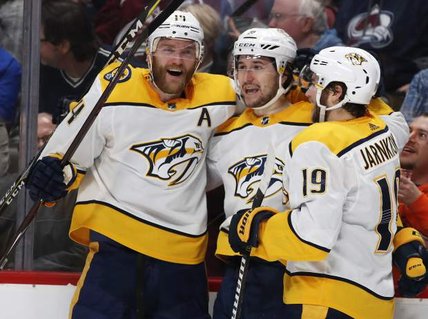 Nashville Predators left wing Filip Forsberg, center, celebrates his game-winning goal with defenseman Mattias Ekholm, left, and center Calle Jarnkrok in overtime of an NHL hockey game against the Colorado Avalanche, Sunday, March 4, 2018, in Denver. The Predators won 4-3 in overtime. (AP Photo/David Zalubowski)
