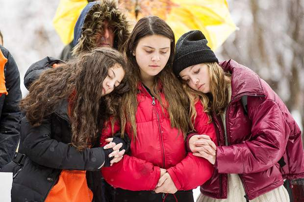 Sophomores Louise Lipsey, left, and Lourdes Ferreira, center, and Naomi Sherman listen to speakers at Paepcke Park on Friday for a student-organized walkout addressing all of the school shootings and gun control.