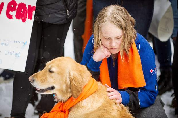 Aspen High School senior Isabella Johansson and Lily the retriever listen to speakers at Paepcke Park on Friday for a student-organized walkout addressing all of the school shootings and gun control.