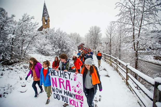 Students of Aspen High School marching on April 20, 2018 on their way to Paepcke Park in downtown Aspen for a student-organized walkout addressing all of the school shootings. The orange was worn to honor the Parkland, Florida victims, as it is their school color.