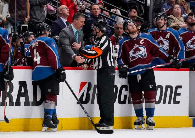 Colorado Avalanche head coach Jared Bednar talks with referee Wes McCauley (4) to challenge a non-goal call during the second period in Game 6 of an NHL hockey first-round playoff series against the Nashville Predators, Sunday, April 22, 2018, in Denver. (AP Photo/Jack Dempsey)