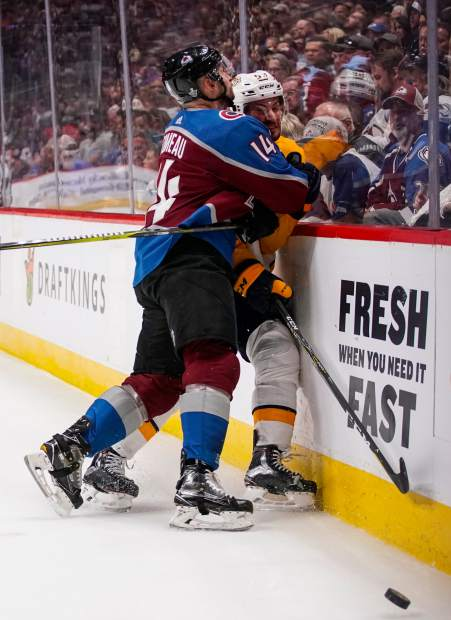Colorado Avalanche left wing Blake Comeau (14) checks Nashville Predators defenseman Roman Josi (59) into the boards during the second period in Game 6 of an NHL hockey first-round playoff series Sunday, April 22, 2018, in Denver. (AP Photo/Jack Dempsey)