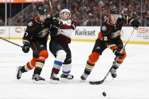 Anaheim Ducks' Josh Manson, right, chases the puck as Colorado Avalanche's Nathan MacKinnon, center, is shoved by Ducks' Hampus Lindholm, of Sweden, during the first period of an NHL hockey game Sunday, April 1, 2018, in Anaheim, Calif. (AP Photo/Jae C. Hong)