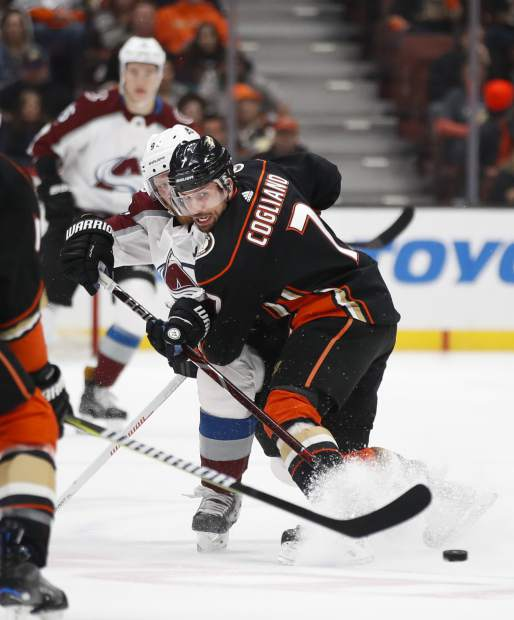 Colorado Avalanche's Gabriel Landeskog, left, of Sweden, hits the puck away from Anaheim Ducks' Andrew Cogliano during the first period of an NHL hockey game Sunday, April 1, 2018, in Anaheim, Calif. (AP Photo/Jae C. Hong)