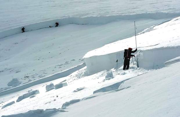 Scott Toepfer, right, a member of the Colorado Avalanche Information Center, takes depth measurements every 50 feet at the crown of an avalanche on April 21, 2013. In the backround are Brian Lazar and John Snook, who walk along the crown to find an area to dig a snow pit to investigate the layers of snow where the avalanche broke off. The deadly avalanche occurred in an area known as Sheep Creek near Loveland Pass, killing five snowboarders.