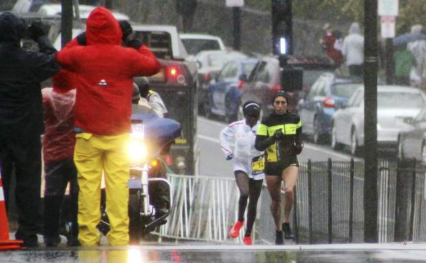 Desiree Linden, right, of Washington, Mich., takes the lead from Gladys Chesir, of Kenya, in the women's division of the 122nd Boston Marathon on Monday, April 16, 2018, in Boston. Linden won to become the first American woman to win the race since 1985. (AP Photo/Jennifer McDermott)