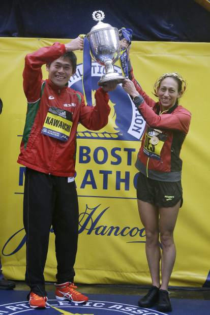 Yuki Kawauchi, left, of Japan, and Desiree Linden, of Washington, Mich., hoist the trophy after winning the men's and women's division of the 122nd Boston Marathon on Monday, April 16, 2018, in Boston. Kawauchi is the first Japanese man to win the race since 1987, and Linden is the first American woman to win the race since 1985. (AP Photo/Elise Amendola)