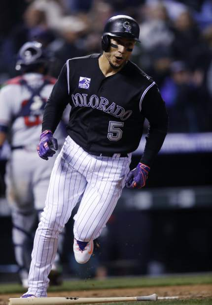 Colorado Rockies' Carlos Gonzalez touches home plate to score the winning run after Tony Wolters drew a bases-loaded walk off Atlanta Braves relief pitcher Arodys Vizcaino in the 10th inning of a baseball game Saturday, April 7, 2018, in Denver. Colorado won 3-2. (AP Photo/David Zalubowski)