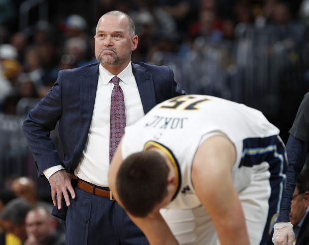 Denver Nuggets coach Michael Malone watches the first half of the team's NBA basketball game against the Milwaukee Bucks on Sunday, April 1, 2018. (AP Photo/David Zalubowski)