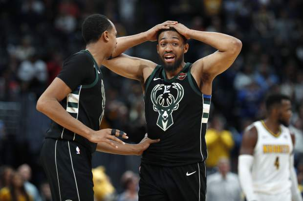 Milwaukee Bucks center John Henson, left, consoles forward Jabari Parker after he missed a shot and did not get a foul call against the Denver Nuggets, at the end of overtime of an NBA basketball game Sunday, April 1, 2018. The Nuggets won 128-125. (AP Photo/David Zalubowski)