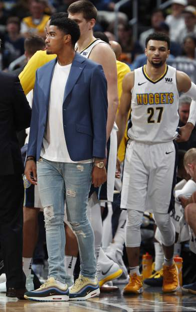 Injured Denver Nuggets guard Gary Harris stands near the bench as his team takes a timeout in the first half of an NBA basketball game against the Milwaukee Bucks on Sunday, April 1, 2018. (AP Photo/David Zalubowski)