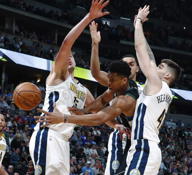 Milwaukee Bucks forward Giannis Antetokounmpo passes the ball as Denver Nuggets center Nikola Jokic, left, and forwards Trey Lyles and Juan Hernangomez, right, defend during the first half of an NBA basketball game Sunday, April 1, 2018, in Denver. (AP Photo/David Zalubowski)