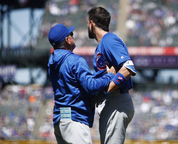 Chicago Cubs manager Joe Maddon, left, helps Kris Bryant after Bryant took a pitch from Colorado Rockies starter German Marquez to the helmet in the first inning of a baseball game Sunday, April 22, 2018, in Denver. Bryant was forced to leave the game. (AP Photo/David Zalubowski)
