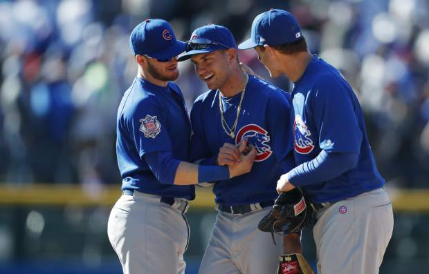 Chicago Cubs center fielder Albert Almora Jr., center, is congratulated by third baseman Ian Happ, left, and first baseman Anthony Rizzo after the Cubs stopped the Colorado Rockies in the ninth inning of a baseball game Sunday, April 22, 2018, in Denver. The Cubs won 9-7. (AP Photo/David Zalubowski)