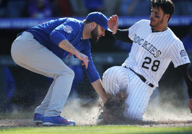 Chicago Cubs relief pitcher Brandon Morrow, left, tags out Colorado Rockies' Nolan Arenado at home plate as he tries to advance to score but instead becomes the final out in the bottom of the ninth inning.
