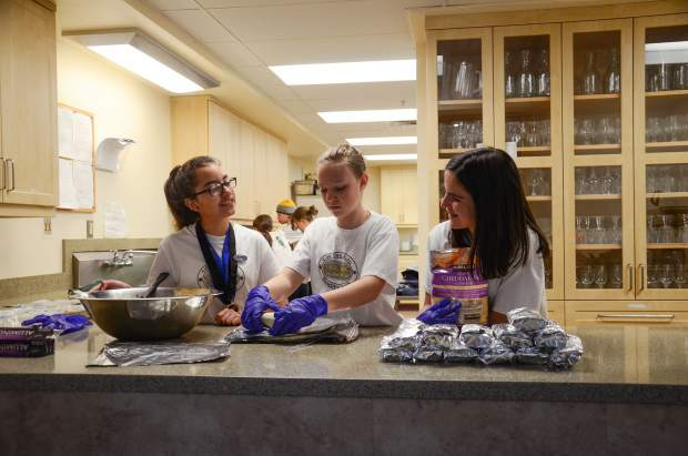 Destination Imagination teammates, from left, Brianna Contreras, Katelyn Brennan and Cailey Cashion make burritos Friday at St. Stephen's Catholic Church to sell as a fundraiser for their team competition trip to Tennessee next month.