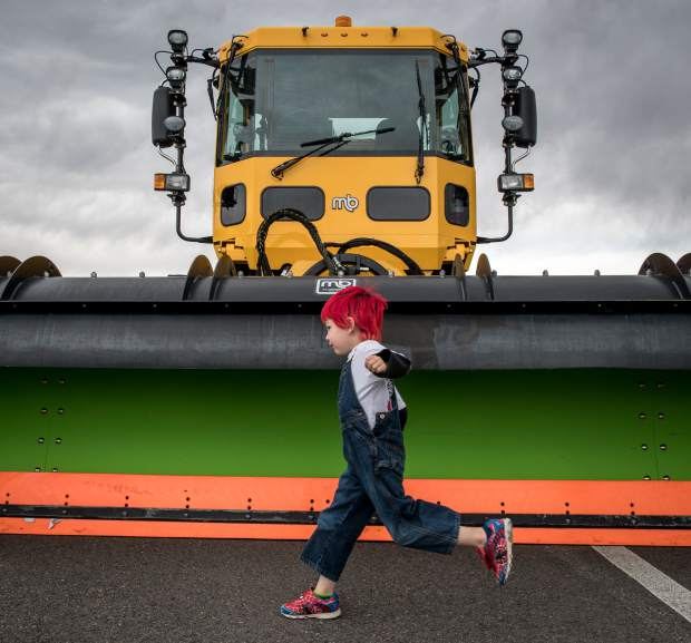 Four-year-old Carl Sirotec has fun running around the airport snow plows with his friends during the annual school field trip day at the Rifle-Garfield County Airport on Thursday.