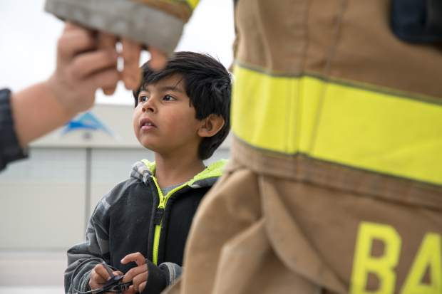 Four-year-old Carlito Salazar listens to speakers at the Rifle-Garfield County Airport during the annual school field trip day.