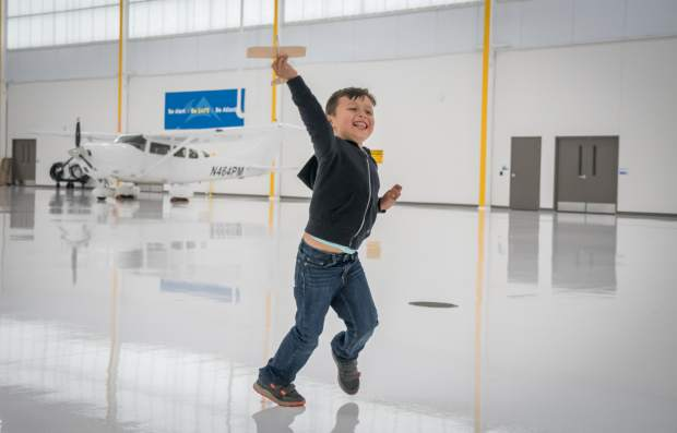 Four-year-old Martin Benavides runs around with his toy airplane inside the hangar at the Rifle-Garfield County Airport during the annual field trip day on Thursday.