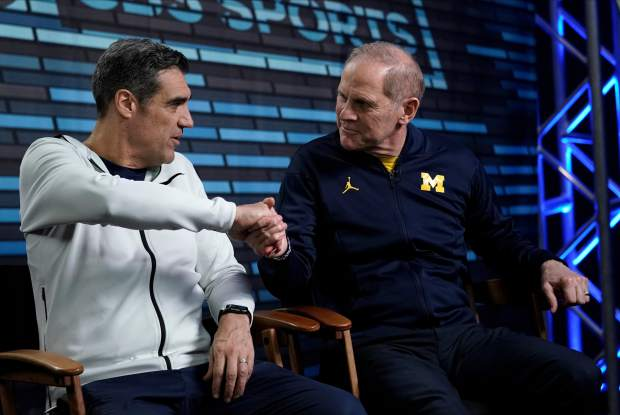 Villanova head coach Jay Wright, left, and Michigan head coach John Beilein shake hands during an interview for CBS Sports Network's