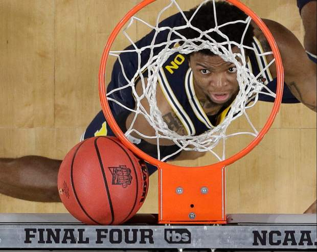 Michigan's Zavier Simpson looks as the ball gets stuck between the basket and the backboard during the first half in the championship game of the Final Four NCAA college basketball tournament against Villanova, Monday, April 2, 2018, in San Antonio. (AP Photo/David J. Phillip)