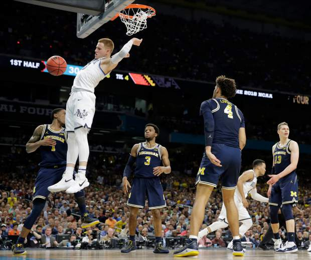 Villanova guard Donte DiVincenzo dunks the ball over Michigan guard Charles Matthews, left, during the first half in the championship game of the Final Four NCAA college basketball tournament, Monday, April 2, 2018, in San Antonio. (AP Photo/Eric Gay)