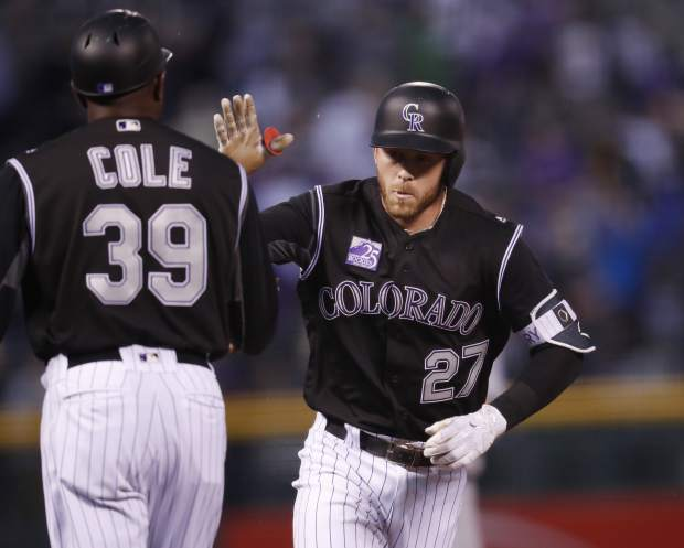 Colorado Rockies third base coach Stu Cole, left, congratulates Trevor Story as he circles the bases after hitting a two-run home run off San Diego Padres starting pitcher Bryan Mitchell in the first inning of a baseball game Monday, April 23, 2018, in Denver. (AP Photo/David Zalubowski)