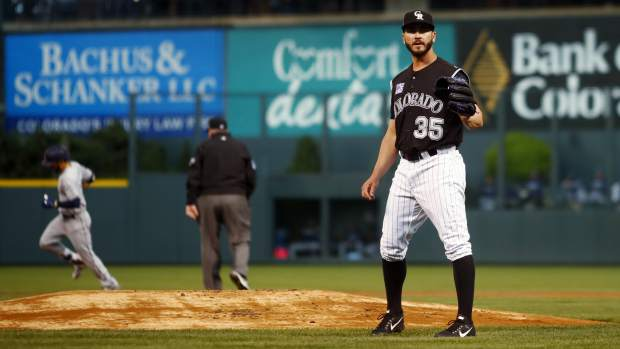 Colorado Rockies starting pitcher Chad Bettis, front, calls for a new ball after giving up a two-run home run to San Diego Padres' Carlos Asuaje in the first inning of a baseball game Monday, April 23, 2018, in Denver. (AP Photo/David Zalubowski)