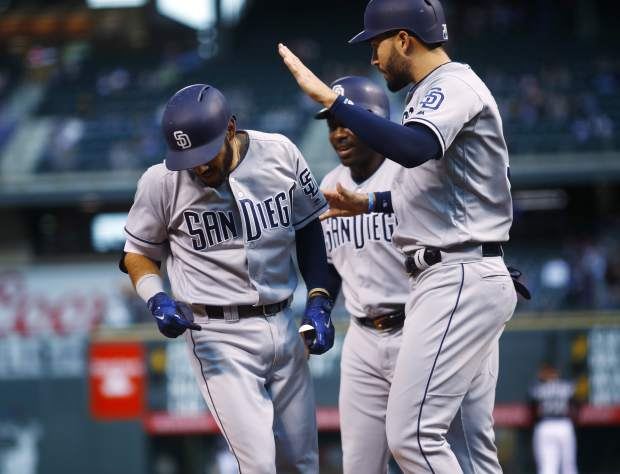 San Diego Padres' Carlos Asuaje, left, is congratulated by Eric Hosmer, front right, and Jose Pirela while crossing home plate after hitting a three-run home run off Colorado Rockies starting pitcher Chad Bettis in the first inning of a baseball game Monday, April 23, 2018, in Denver. (AP Photo/David Zalubowski)