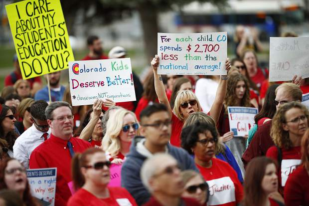 Teachers hold placards during a rally outside the state Capitol, Monday, April 16, 2018, in Denver. Teachers from around the state were on hand to demand better salaries as lawmakers under the dome were set to debate a pension reform measure to cut retirement benefits as well as take-home pay. (AP Photo/David Zalubowski)