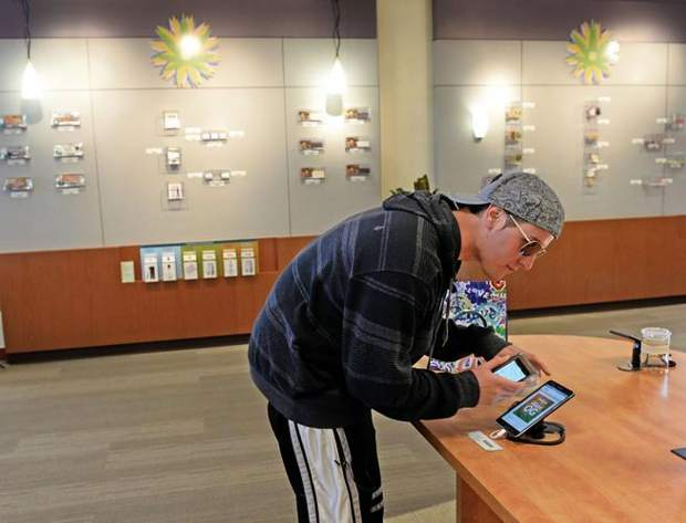 A customer researches marijuana strains at Euflora, the first retail marijuana store in Aurora, on Oct. 13, 2014. (Kathryn Scott Osler, Denver Post file)