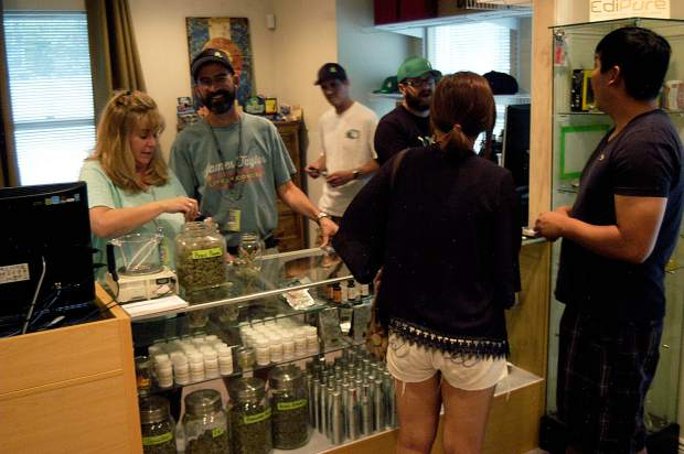 Cheryl and Dan Sullivan, at left, owners of the Green Joint recreational marijuana store in Glenwood Springs, work behind the counter during August 2014.