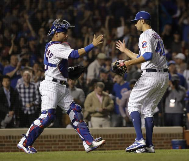 Chicago Cubs catcher Willson Contreras, left, and relief pitcher Steve Cishek celebrate the Cubs' 3-2 win over the Colorado Rockies after a baseball game Monday, April 30, 2018, in Chicago. (AP Photo/Charles Rex Arbogast)