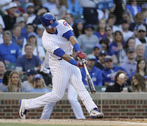 Chicago Cubs' Addison Russell hits an RBI single off Colorado Rockies starting pitcher Kyle Freeland during the second inning of a baseball game Monday, April 30, 2018, in Chicago. Ben Zobrist scored on the play. (AP Photo/Charles Rex Arbogast)