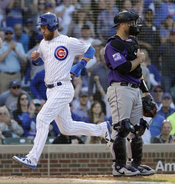 Chicago Cubs' Ben Zobrist,left, scores past Colorado Rockies catcher Chris Iannetta off a single by Addison Russell during the first inning of a baseball game Monday, April 30, 2018, in Chicago. (AP Photo/Charles Rex Arbogast)