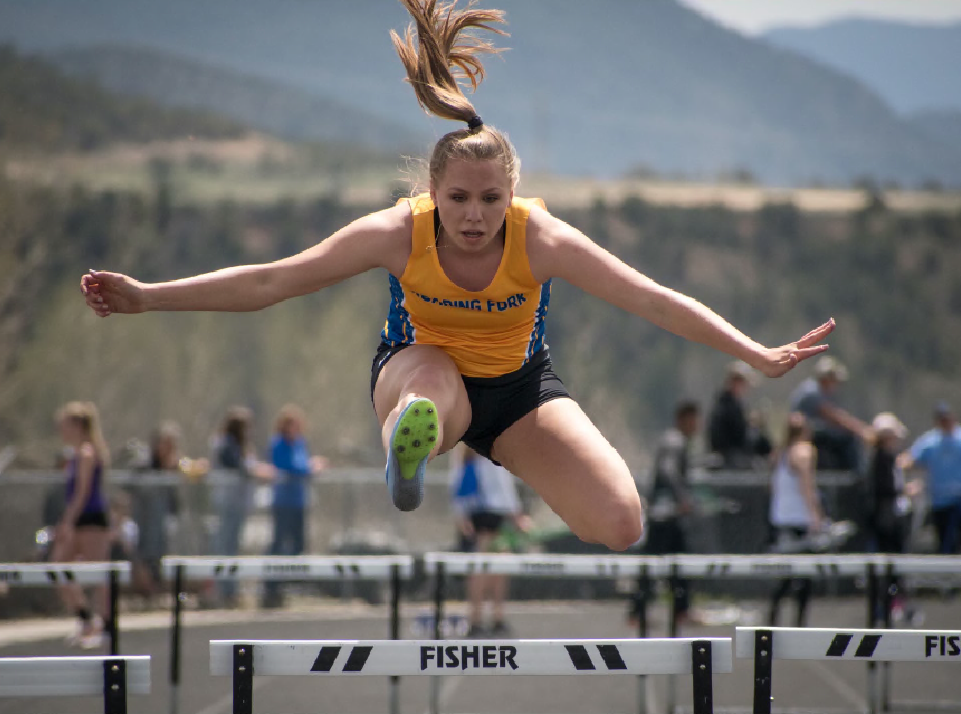 Roaring Fork junior Kendall Bernot leaps over a hurdle during an event Thursday at the Coal Ridge Invitational in New Castle. See Sports for a full story.