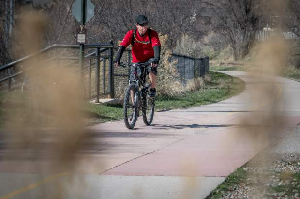 A bicyclist makes his way through Glenwood Springs on the Rio Grande Trail on a sunny but chilly Tuesday afternoon.