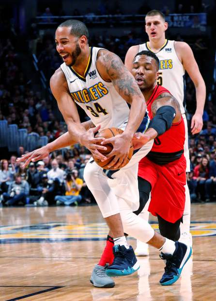 Portland Trail Blazers guard Damian Lillard (0) knocks the ball loose form the hands of Denver Nuggets guard Devin Harris (34) during the first quarter of an NBA basketball game Monday, April 9, 2018, in Denver. (AP Photo/Jack Dempsey)