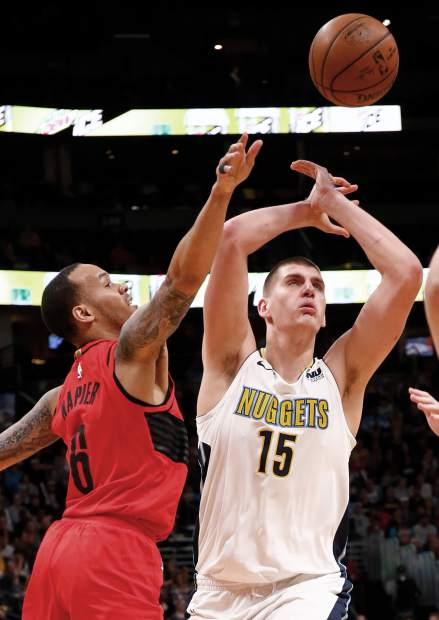 Portland Trail Blazers guard Shabazz Napier (6) knocks the ball from Denver Nuggets center Nikola Jokic (15) during the first quarter of an NBA basketball game Monday, April 9, 2018, in Denver. (AP Photo/Jack Dempsey)