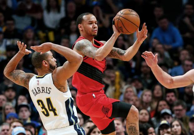 Portland Trail Blazers guard Shabazz Napier, center, passes around Denver Nuggets guard Devin Harris (34) during the first quarter of an NBA basketball game Monday, April 9, 2018, in Denver. (AP Photo/Jack Dempsey)