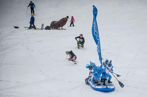 The Shaboomee Snow Sharks make their way down on an oversized stand up paddleboard on Sunday at Snowmass for Schneetag on closing weekend.